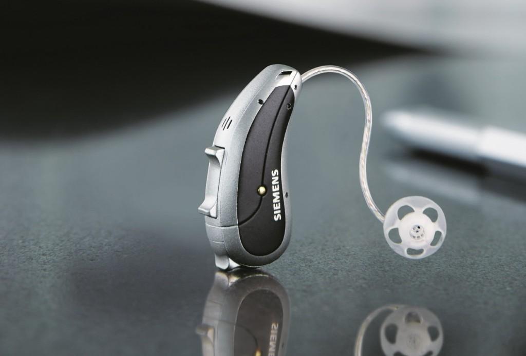 """Gamintojų išmanioji sistema """"EasyTek"""" per """"Bluetooth"""" ryšį sujungia klausos aparatus su disku, dėvimu aplink kaklą. Naudojant šį diską galima išjungti ir įjungti aparatą, reguliuoti garsą ir kitus parametrus."""